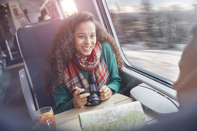 Young woman with camera and map riding train