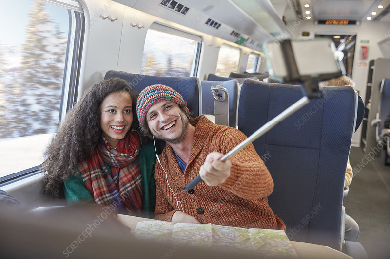 Happy young couple taking selfie on train