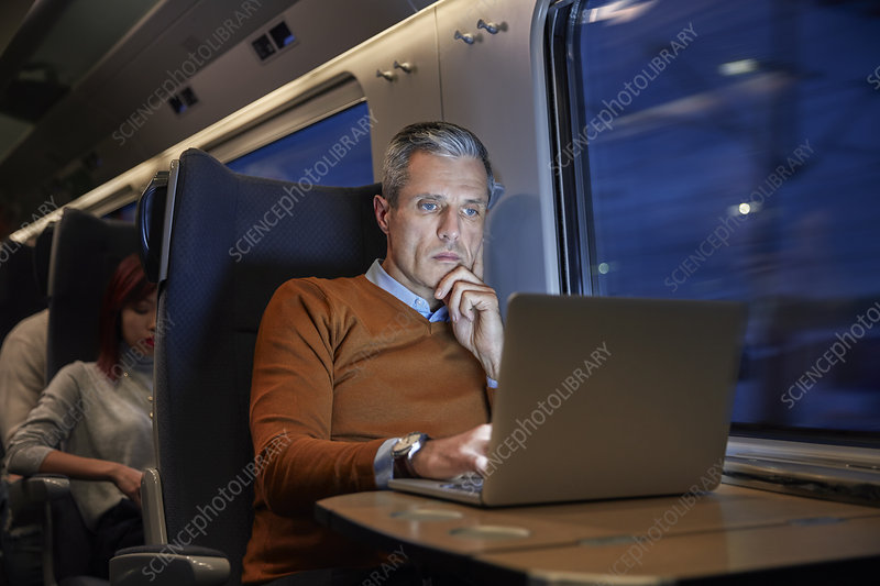 Focused businessman working at laptop on train