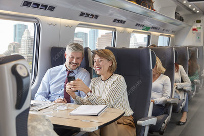 Business people using smartphone on train