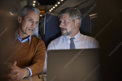 Businessmen talking, working at laptop on train