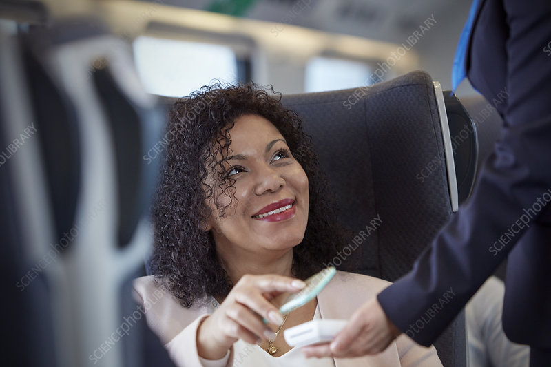 Smiling woman using contactless payment on train