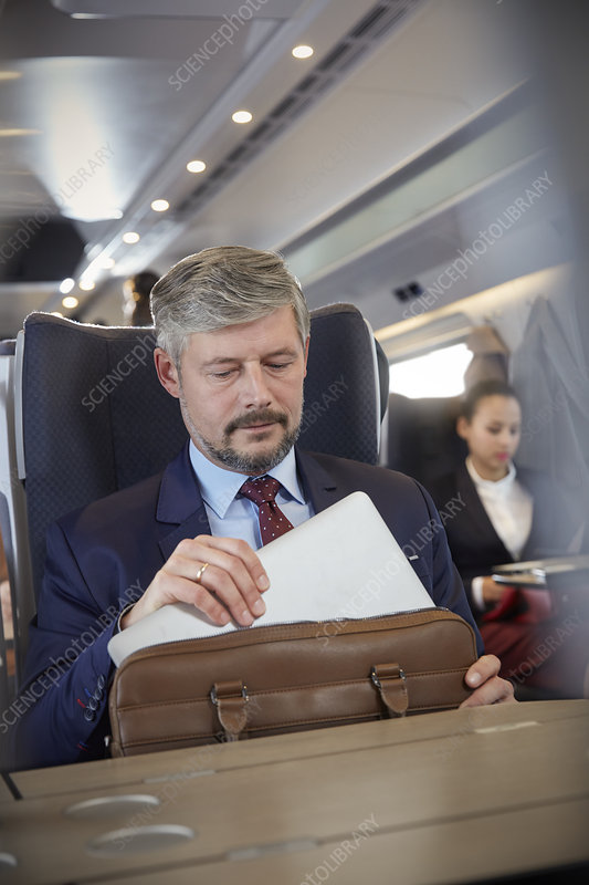 Businessman removing laptop from briefcase