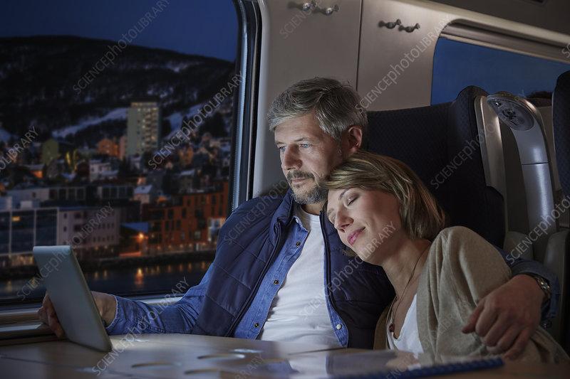 Affectionate wife sleeping on husband on train