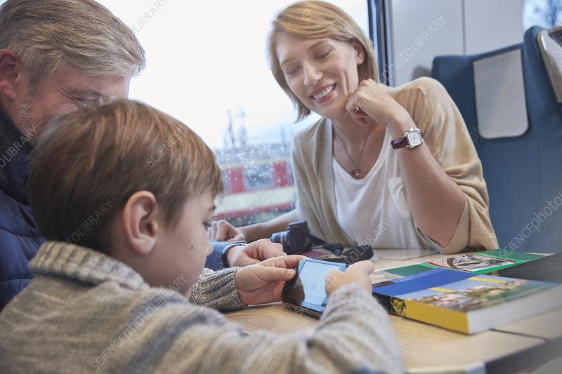 Family using smart phone on train