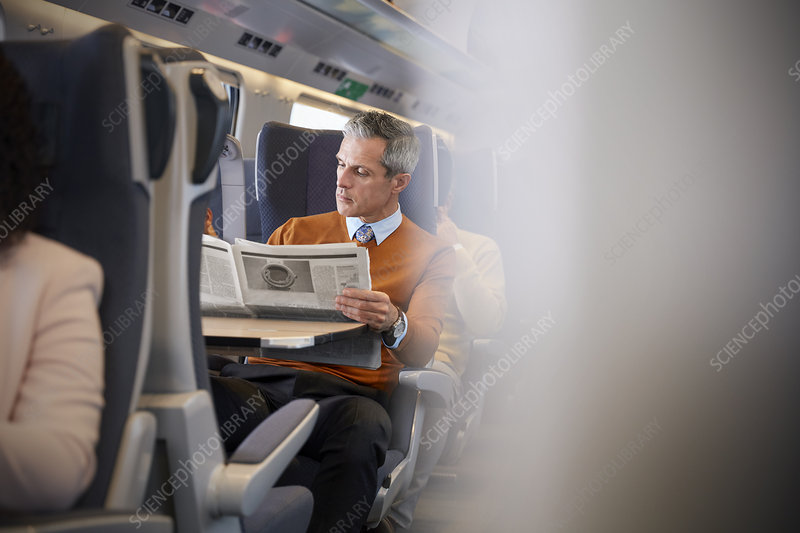Businessman reading newspaper on train