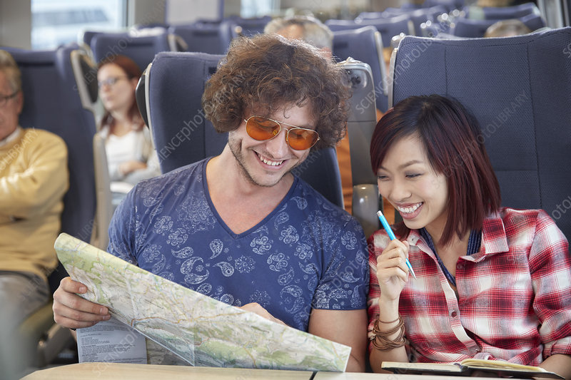 Young couple looking at map on train