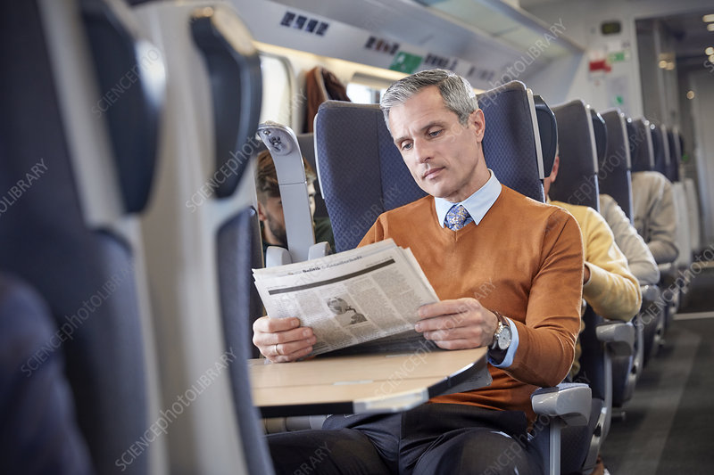 Businessman reading newspaper on train