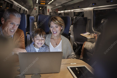 Family using laptop on train at night