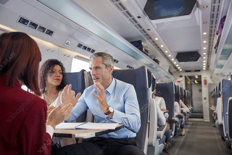 Business people working, talking on train