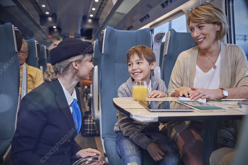 Attendant talking with mother and son on train