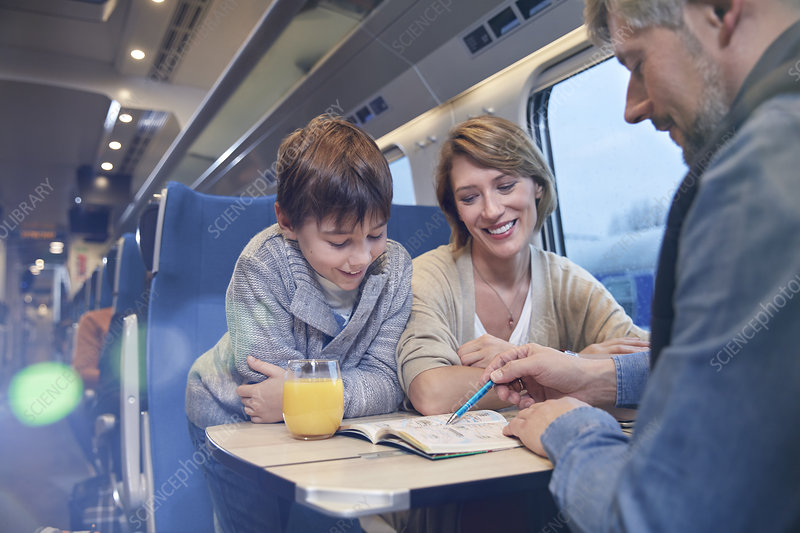 Family looking at travel guidebook on train