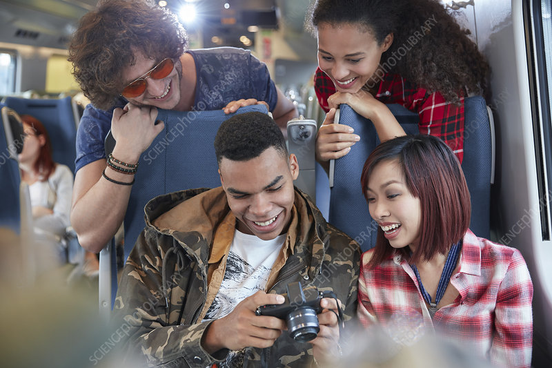 Young friends looking at photos on train