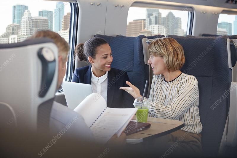 Businesswomen working, talking on train