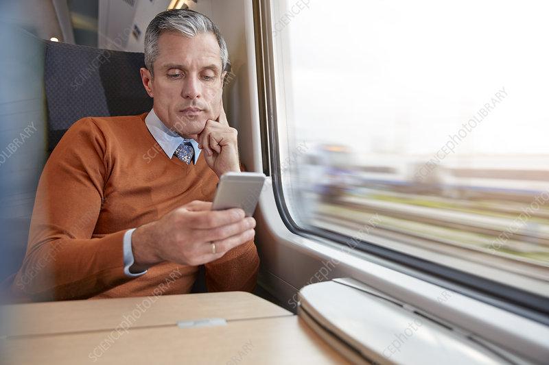 Businessman using smart phone at train window