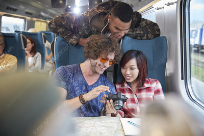 Young friends looking at photographs on train