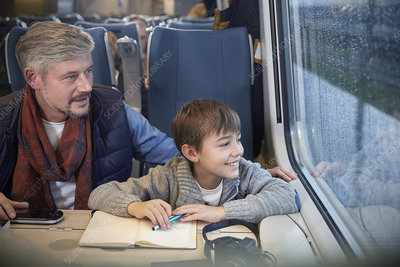 Father and son looking out window on train