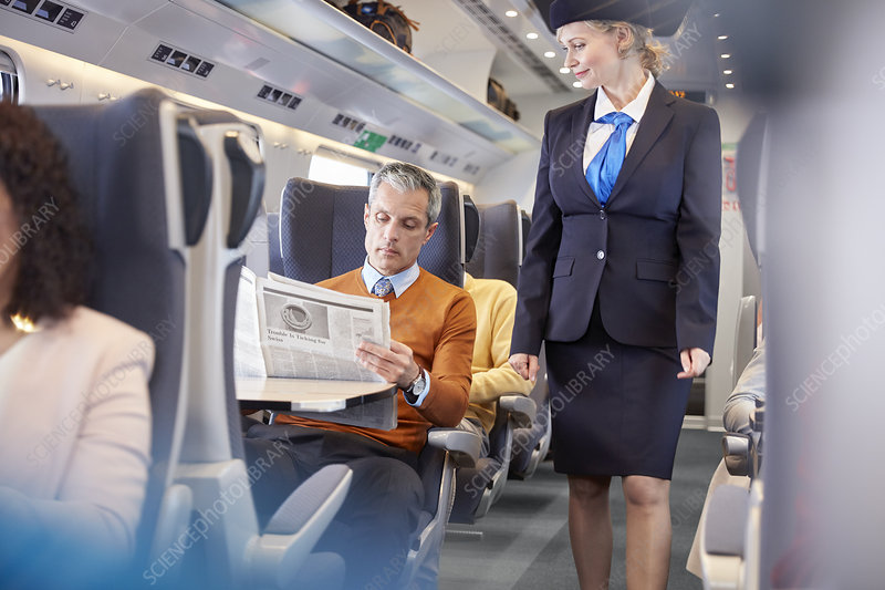 Attendant checking on businessman on train