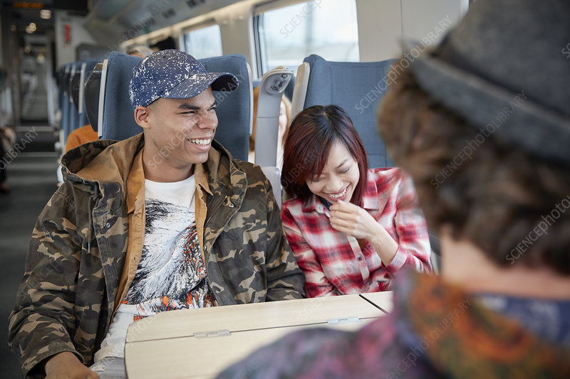 Young couple laughing on train