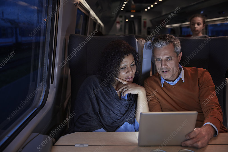 Couple using digital tablet on dark train at night