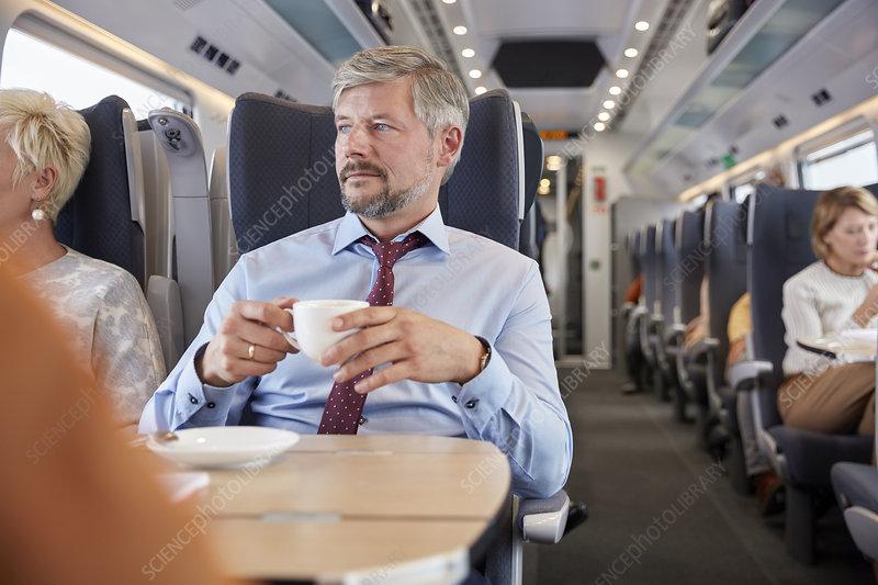 Businessman drinking coffee on train