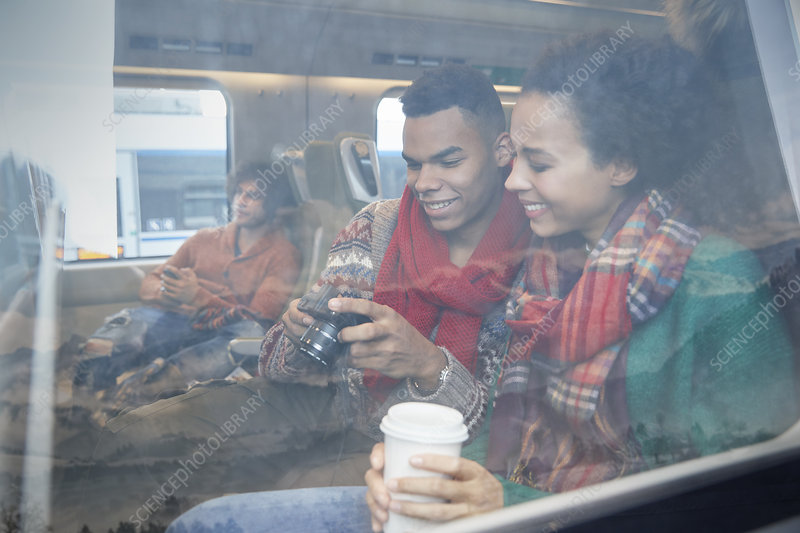 Young couple with coffee on train