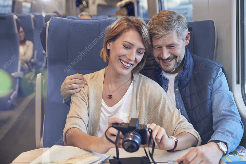 Couple looking at photographs on train
