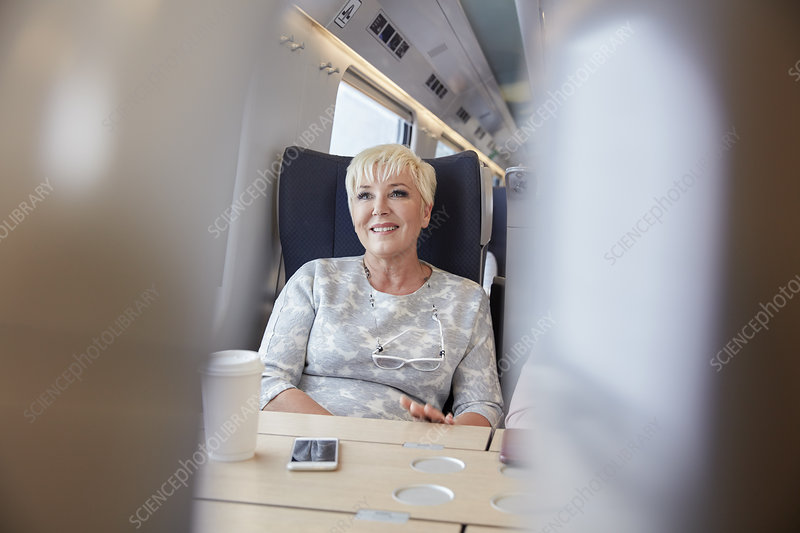 Smiling, confident businesswoman on train
