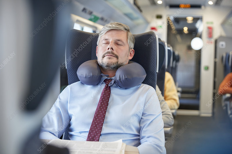 Tired businessman with neck pillow on train