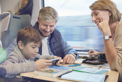 Smiling family with travel guidebooks on train
