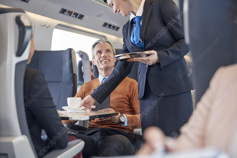 Attendant serving coffee to businessman on train