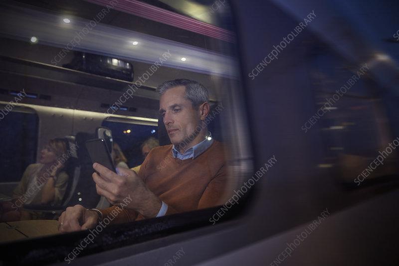 Businessman using smart phone at window on train