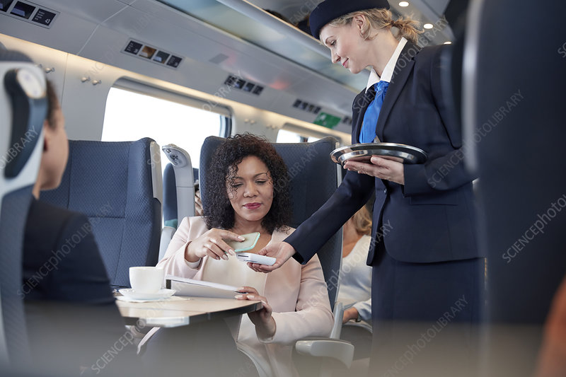 Businesswoman using contactless payment on train