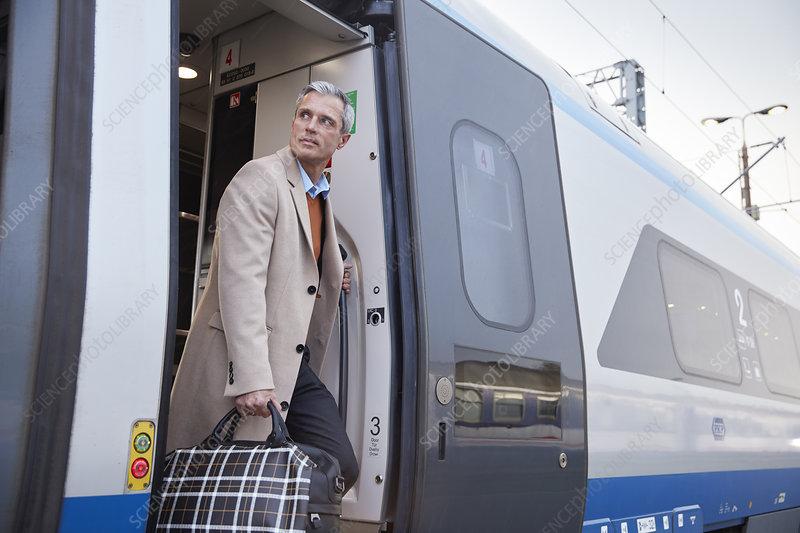 Businessman getting off train