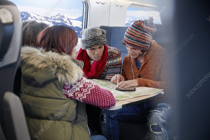 Young friends with map planning on train