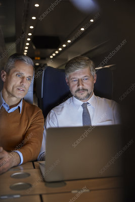 Businessmen working at laptop on train at night