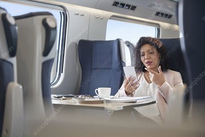 Businesswoman video chatting on train