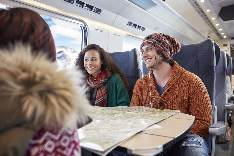 Smiling young friends planning with map on train