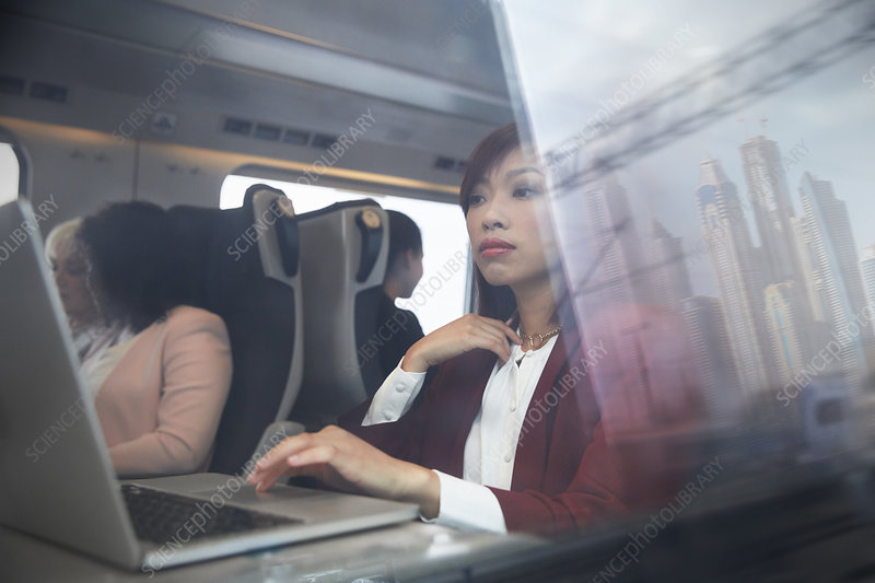 Focused businesswoman working at laptop on train