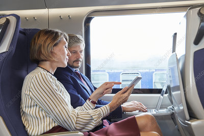 Businessman and businesswoman working on train