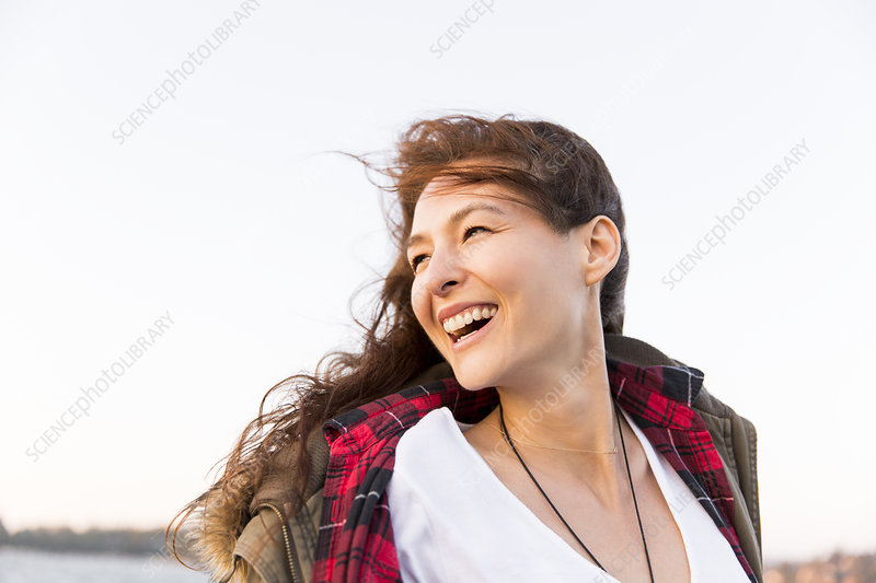 Smiling, enthusiastic woman looking over shoulder