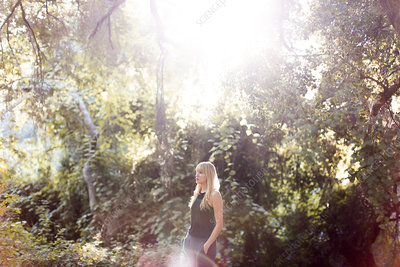 Serene woman standing in sunny summer woods