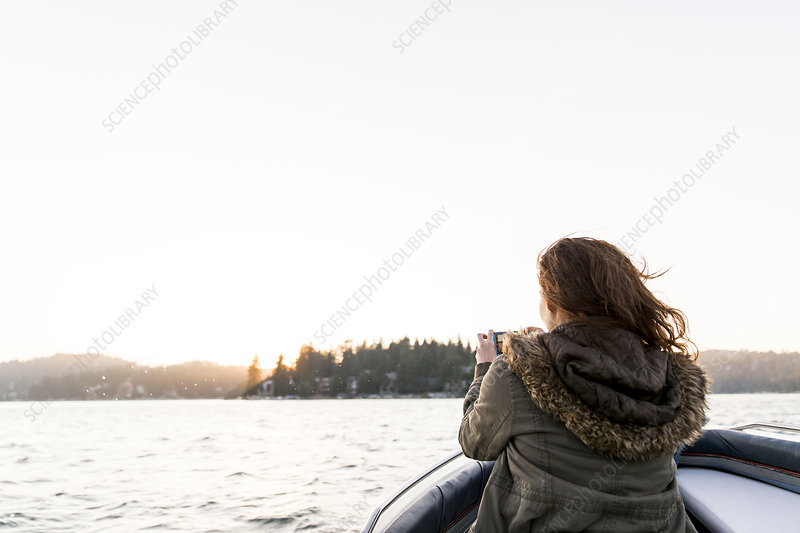 Woman photographing tranquil lake