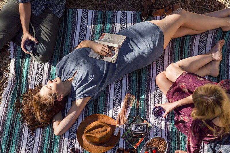 Young woman with book relaxing on picnic blanket