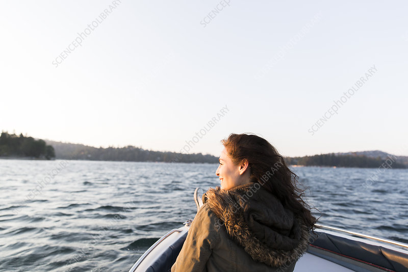 Smiling woman boating on sunny, tranquil lake