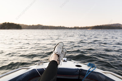 Personal perspective woman boating with feet up