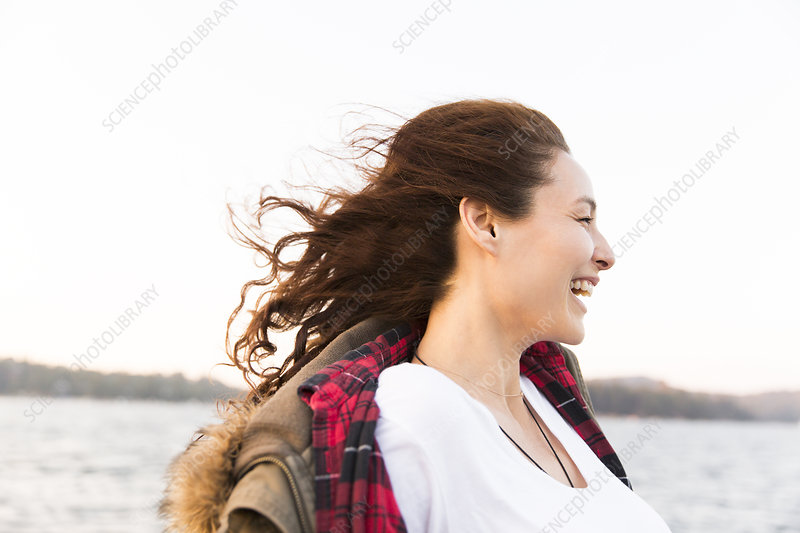 Smiling, carefree woman at windy lakeside