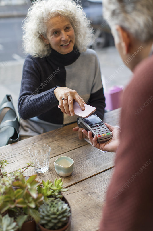 Woman using smart phone contactless payment
