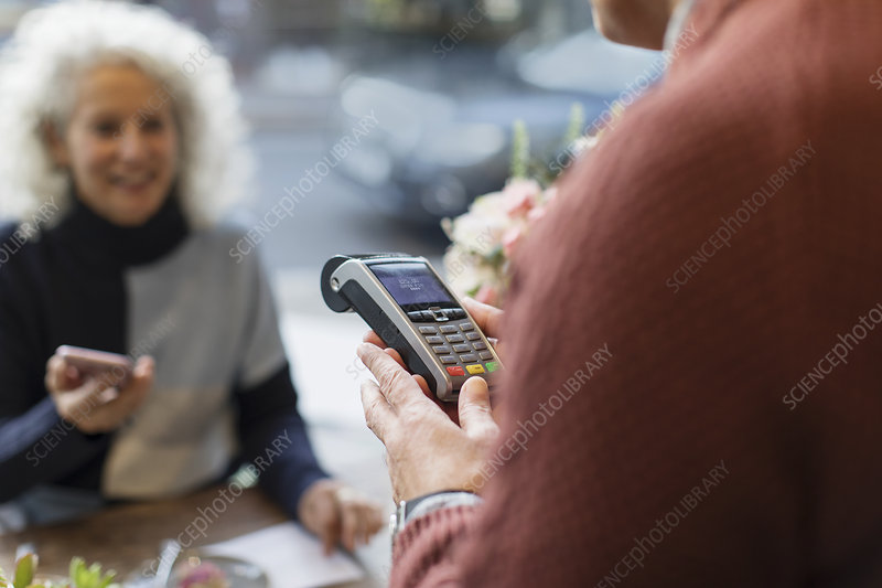 Cashier with machine ready for contactless payment