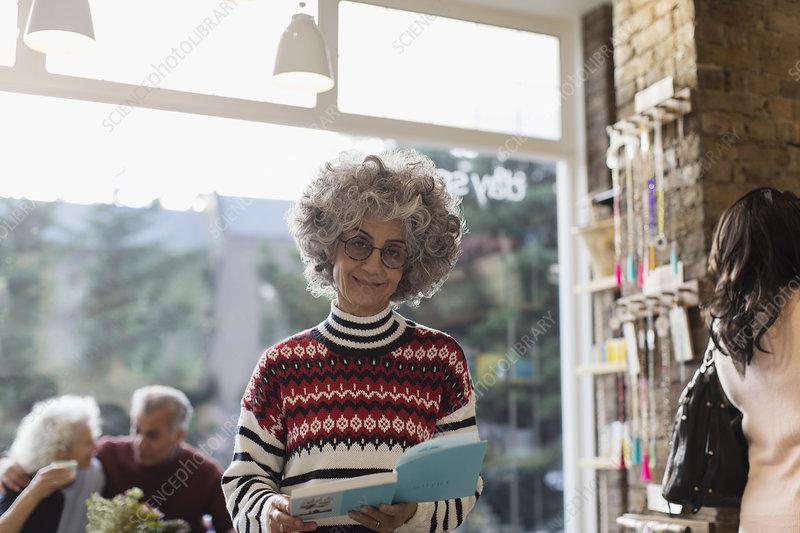 Portrait smiling senior woman reading book